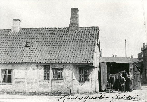 """Bagsiden af """"Stenhuggergården"""", hvor smed Svendsen tog imod. Ca. 1900."""