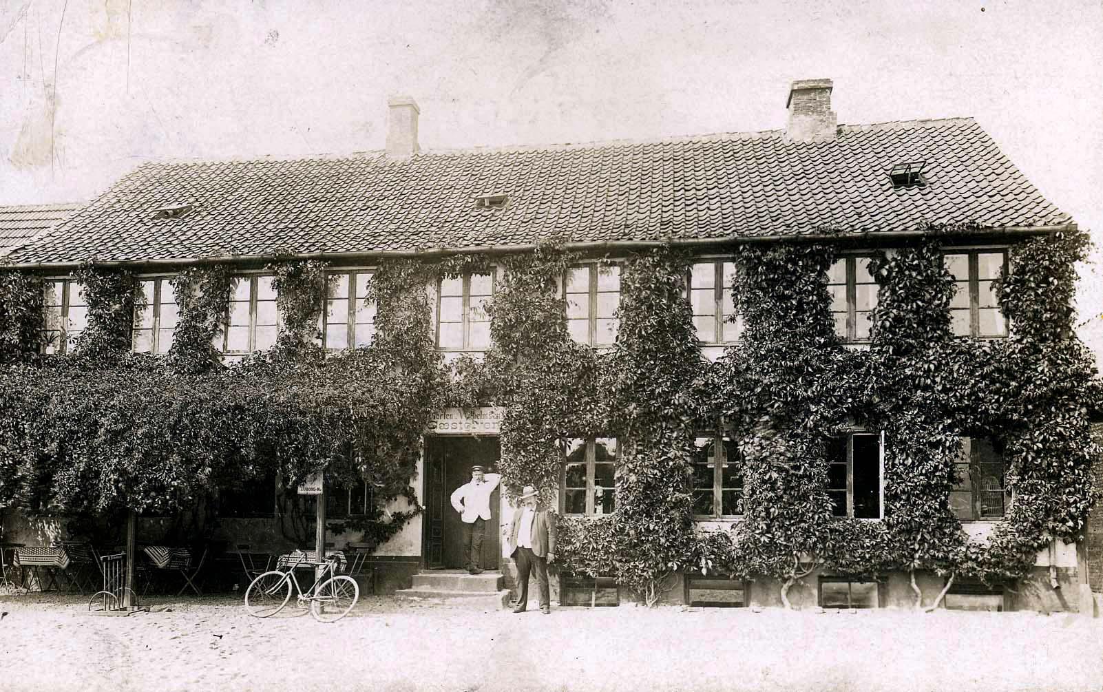 Gammel Landbohjem i Slangerupgade 6, dækket i efeu. Det skulle angiveligt være værten selv, der ses foran værtshuset