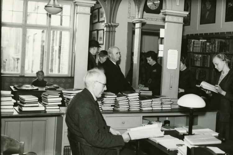 Overbibliotekar Anders Uhrskov betjener lånere på Hillerød Bibliotek, Nordre Jernbanevej 6 med  Ca. 1955