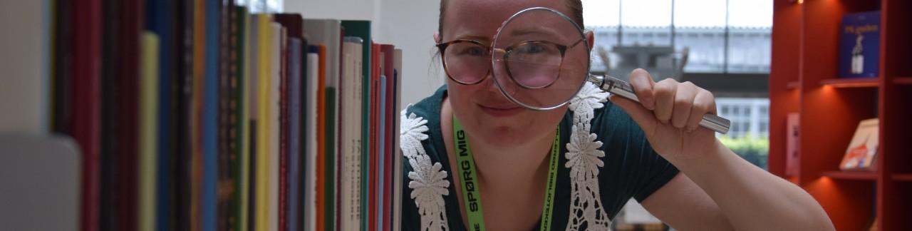 Bibliotekar Julie Feldskov Henriksen kigger gennem lup ved bogreol