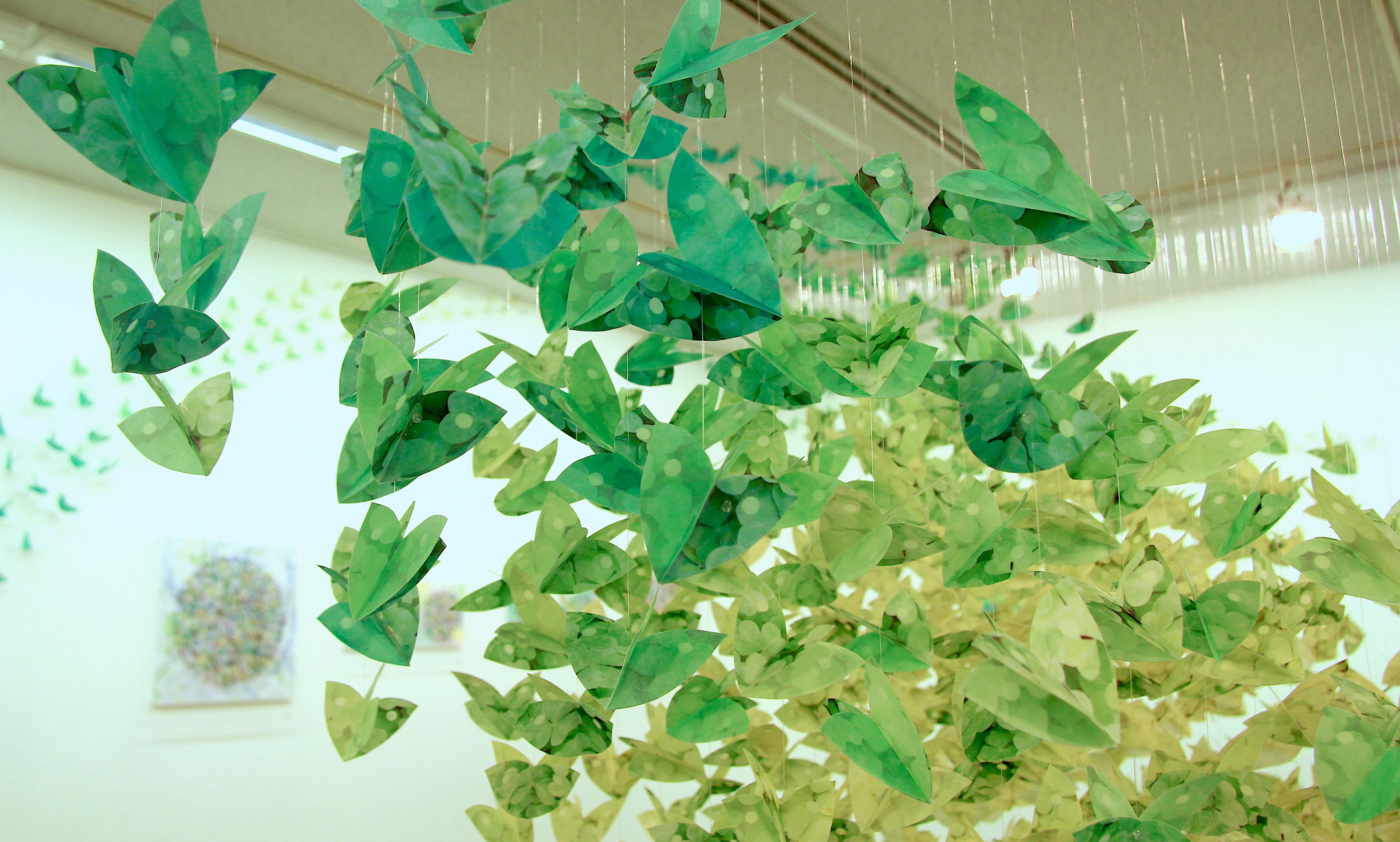 Hundredevis af grønne papirblade i forskellige nuancer i hvirvlende formation