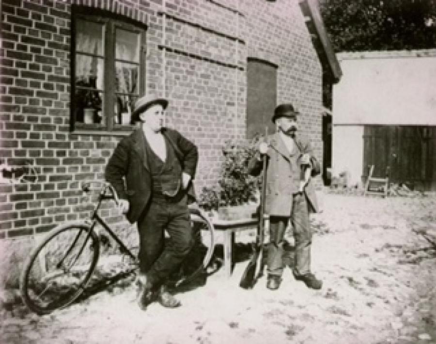 Hjulmand Hans Vilhelm Petersen med gevær og langpibe sammen med en kammerat i gården til Hjulmandens Hus.