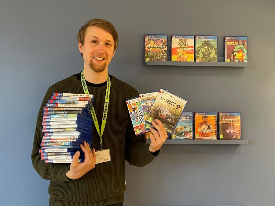 Bibliotekar Jacob Refstrup Hansen med stakkevis af Playstation-spil