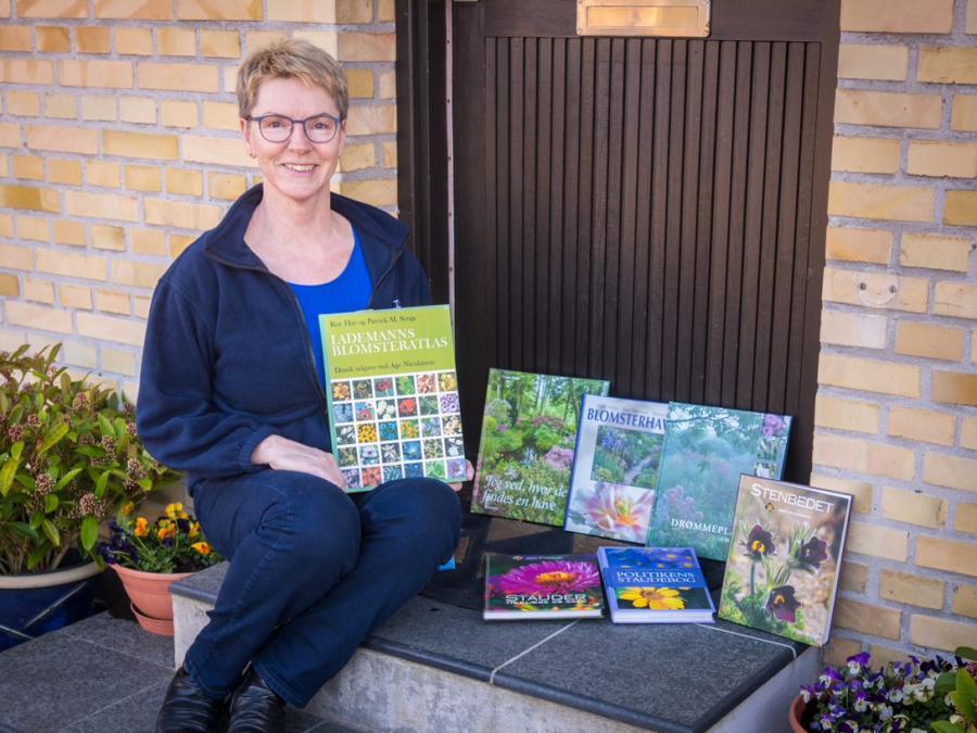 Biblioteksassistent Lene Hansen på sit dørtrin omgivet af havebøger