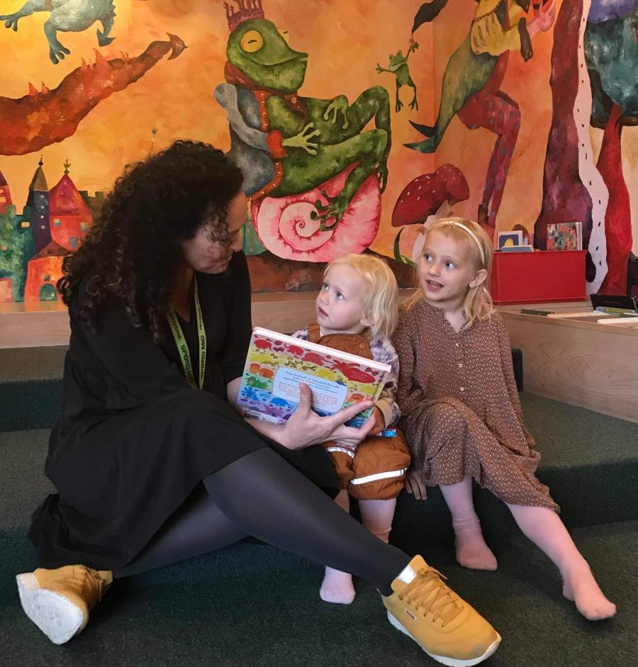 Børnebibliotekar Pia Nyberg læser højt for to piger i børnebibliotekets legerum