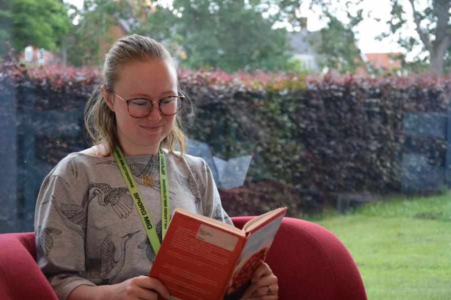 Julie Feldskov Henriksen i lænestol med bog