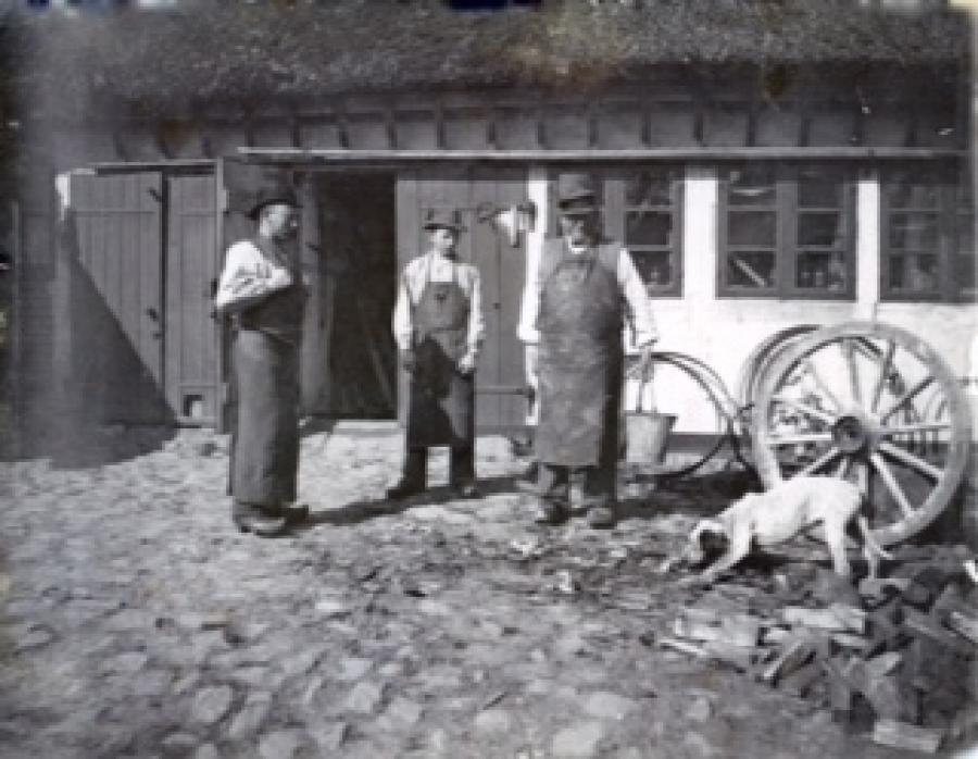 Den unge Hans Vilhelm Petersen sammen med den ældre Hans Pedersen i hjulmandens gård sammen med en svend.