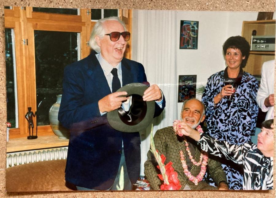 Niels Macholm omgivet af glade gæster til fest i sit hjem
