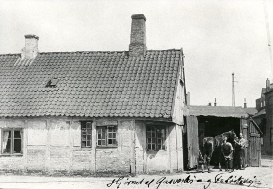 """Gasværksvej(i dag Frederiksgade). Bagsiden af """"Stenhuggergården"""" med smeden Svendsen. Ca. 1900."""